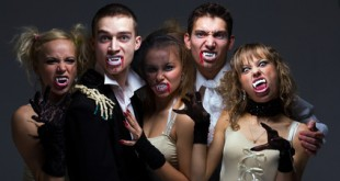 Portrait of hungry vampire family on a gray background